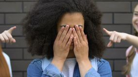 Depressed african american girl crying, victim of racial bullying at school
