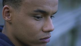 Depressed african-american guy thinking about his life, lonely sitting outdoor. Stock footage stock footage