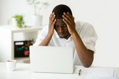 Depressed African American worker upset with company crisis. Sad depressed worker feeling down after company business failure, losing money, becoming bankrupt Stock Photo
