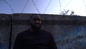 Depressed afro-american man standing near barbed wire fence, refugee camp. Stock footage stock video
