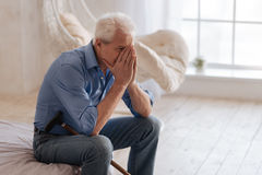 Depressed aged man crying. I can not hold my feelings. Depressed emotional aged man sitting on the bed and covering his face while crying stock images