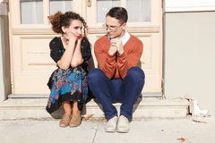 Depressed and agitated man and woman crouching in front of the h Royalty Free Stock Photography