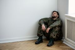 Depressed army man in uniform sitting in a corner of an empty room. Place for your poster on the wall stock photo