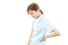 Depressed Asian female nurse. Asian female nurse back Pain Stock Photo
