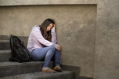 Depressed Asian Korean student woman or bullied teenager sitting outdoors on street staircase overwhelmed and anxious feeling stock images