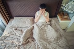 Depressed Asian man blaming on the phone on bed.  Stock Photography
