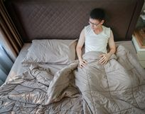 Depressed Asian man suffering on bed in bedroom.  Royalty Free Stock Image