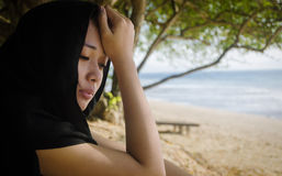 Depressed Asian in the sea shore Royalty Free Stock Photo