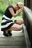 Depressed attractive blonde on the wooden bridge crouching Stock Image