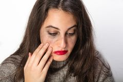 Depressed woman smearing her bright red lipstick. Depressed attractive young brunette woman with a sad expression looking down smearing her bright red lipstick Royalty Free Stock Image