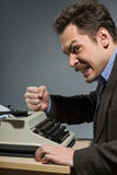 Depressed author sitting at typewriter Royalty Free Stock Photos