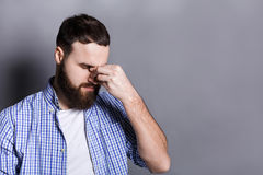Depressed bearded man with closed eyes. Touching his face. Young guy feeling hopeless, having headache, gray studio background, copy space royalty free stock image