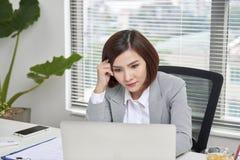 Depressed belastade den unga asiatiska affärskvinnan med bärbar datorsuffe arkivbild