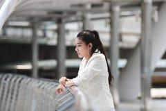 Depressed belastade den unga asiatiska affärskvinnan som lider från problem på det utvändiga kontoret royaltyfria bilder