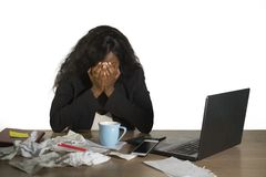 Depressed black African American businesswoman crying sad at office computer desk feeling anxious and overwhelmed surrounded by me. Desperate and depressed black royalty free stock photography