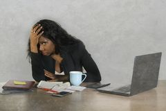 Depressed black African American businesswoman crying sad at office computer desk feeling anxious and overwhelmed surrounded by me. Desperate and depressed black stock photography