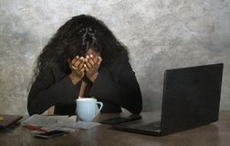 Depressed black African American businesswoman crying sad at office computer desk feeling anxious and overwhelmed surrounded by me royalty free stock image