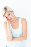 Depressed blonde woman with hand on temple. On white background Royalty Free Stock Photo