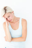 Depressed blonde woman with hand on temple. On white background Stock Images