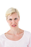 Depressed blonde woman looking at camera. On white background Royalty Free Stock Photos