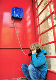 Depressed boy in telephone box Stock Image