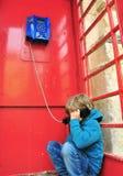 Depressed boy in telephone box. Depressed boy sitting on the floor in telephone box Stock Image