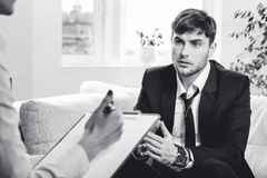 Depressed businesman talking with psychologist Royalty Free Stock Images