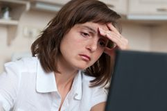 Depressed business person at work. Depressed and tired business woman at work - looking to computer Stock Photo