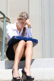 Depressed Business Woman. A upset, depressed business woman sitting outside company Royalty Free Stock Images