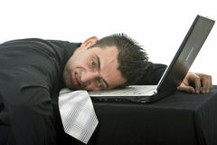 Depressed businessman. Stressed businessman with his head resting on the laptop computer keyboard Royalty Free Stock Photography