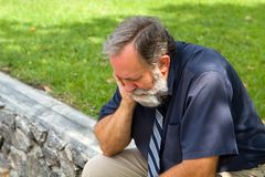 Depressed Businessman. Businessman depressed by economic conditions sits melancholic in a park with his head in his hand Stock Photo
