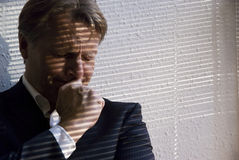 Depressed businessman. A businessman is overcome with stress and grief due to the pressures of the credit crunch or someother bad news Stock Image