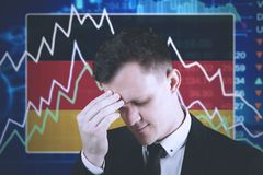 Depressed businessman with declining finance graph. Young businessman having headache with declining finance graph and American flag in the trade stock Stock Image