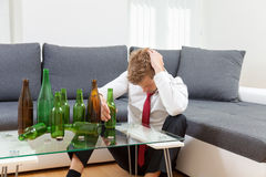 Depressed businessman drunk at home Stock Photography