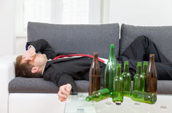 Depressed businessman drunk at home Stock Photos