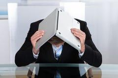 Depressed businessman hiding under his laptop. Depressed businessman sitting at a reflective table hiding under his laptop as he holds it open over his bowed Stock Image