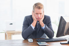 Depressed businessman at his desk. In his office Stock Photography