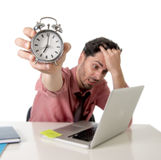 Depressed businessman holding alarm clock sitting at office desk working with computer laptop in deadline project concept Royalty Free Stock Image