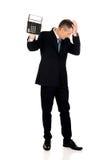 Depressed businessman holding a calculator Stock Photo