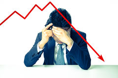 Depressed Businessman holding a gun behind bad Stock market char Stock Photo