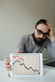 Depressed businessman leaning head below bad stock market chart. In office royalty free stock image