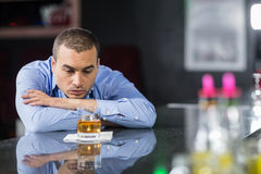Depressed businessman looking at whisky glasses Stock Photo