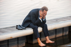 Depressed businessman. Depressed mature businessman holding head in hands while sitting barefoot at the quayside Stock Photo