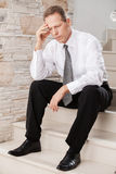 Depressed businessman. Depressed mature man in formalwear holding head in hand while sitting on staircase Stock Photos
