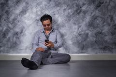 Depressed businessman with mobile phone and sitting on the floor. Young depressed businessman with mobile phone and sitting on the floor Royalty Free Stock Images