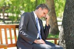Depressed businessman in park. Depressed mature businessman sitting on park bench Royalty Free Stock Image