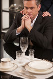 Depressed businessman in restaurant. Disappointed mature man in formalwear sitting at the restaurant and holding his hands on chin while woman holding her hands Royalty Free Stock Image