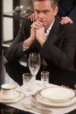 Depressed businessman in restaurant. Royalty Free Stock Image