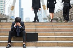 Depressed Businessman sit in city. Sad Businessman sitting on stair of modern city while other Business guys walk. Head down with feeling bad covered face by two Stock Images