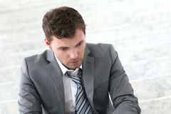 Depressed businessman sitting outdoors Royalty Free Stock Photography